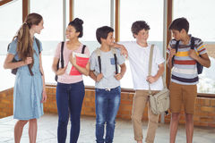 Happy students interacting with each other in corridor. At school Royalty Free Stock Images