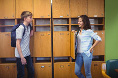 Happy students interacting with each other in locker room stock images