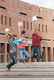 Happy students jumping in the air holding exam Stock Image