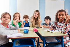 Happy students keep their thumbs up stock photos