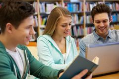 Happy students with laptop and book at library. People, education, technology and school concept - happy students with laptop computer and book in library Stock Images