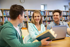 Happy students with laptop and book at library. People, education, technology and school concept - happy students with laptop computer and book talking in Royalty Free Stock Photo
