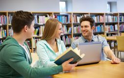 Happy students with laptop and books at library. People, education, technology and school concept - happy students with laptop computer and books in library Royalty Free Stock Photo