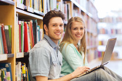 Happy students with laptop in library. People, education, technology and school concept - happy students with laptop computer networking in library Royalty Free Stock Photos