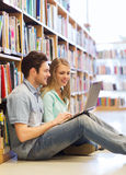 Happy students with laptop in library Stock Images