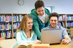 Happy students with laptop in library Royalty Free Stock Image