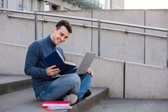 Happy Students learning. Smiling male student learning for the exam  with a laptop on knees, seated on stairs. Smiling Happy student using laptop and reading stock image