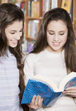 Happy students in library. Happy teen students in library with book Royalty Free Stock Images