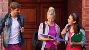 Happy students looking at folder together Royalty Free Stock Photos