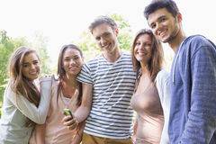 Happy students looking at smartphone outside on campus Stock Photo