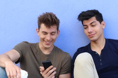 Happy students looking at smartphone outside on campus at the university royalty free stock photography