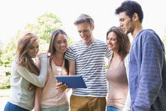Happy students looking at tablet outside on campus Stock Photo