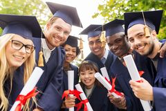 Happy students in mortar boards with diplomas Royalty Free Stock Photography