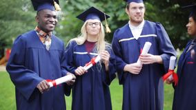 Happy students in mortar boards with diplomas. Education, graduation and people concept - group of happy international students in mortar boards and bachelor stock footage