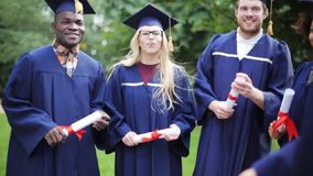 Happy students in mortar boards with diplomas. Education, graduation and people concept - group of happy international students in mortar boards and bachelor stock video