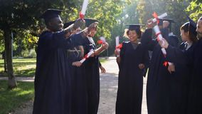 Happy students in mortar boards with diplomas. Education, graduation and people concept - group of happy international students in mortar boards and bachelor stock video footage