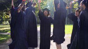 Happy students in mortar boards with diplomas stock video footage