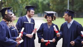 Happy students in mortar boards with diplomas stock video