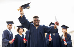 Happy students in mortar boards with diplomas Stock Image