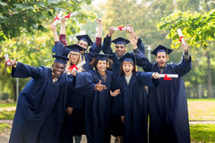Happy students in mortar boards with diplomas Stock Images
