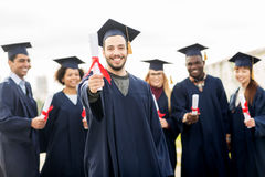 Happy students in mortar boards with diplomas Royalty Free Stock Photo