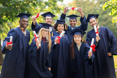 Happy students in mortar boards with diplomas Royalty Free Stock Images