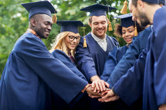 Happy students in mortar boards with hands on top Stock Photography