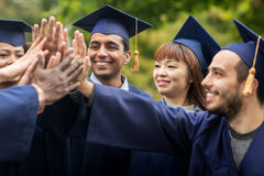 Happy students in mortar boards making high five Stock Photos