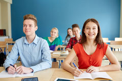 Happy students with notebooks at school Royalty Free Stock Photography