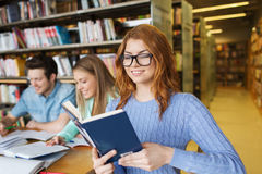 Happy students reading books in library Royalty Free Stock Photo