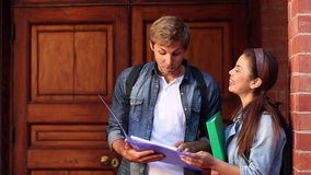 Happy students reading from folder together Royalty Free Stock Photography