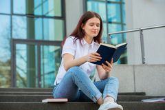 Happy Students relaxing. University student outdoors on Campus sitting on stairs holding books. A confident student holding books over university building stock photography