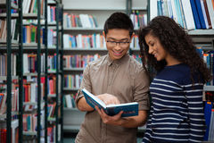 Happy students searching book in library Royalty Free Stock Image