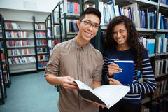 Happy students searching books in library Stock Image