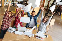 Happy students sitting in library throw up the paper. Stock Photo