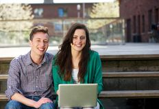 Happy students sitting outdoors with laptop. Portrait of happy students sitting together outdoors with laptop Royalty Free Stock Photo