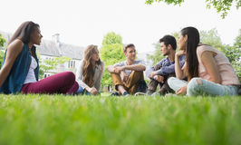 Happy students sitting outside on campus Stock Images