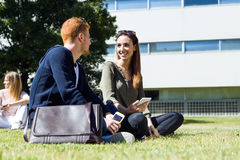 Happy students sitting outside on campus at the university. Stock Photography