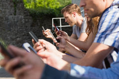 Happy students sitting in a row texting Stock Photo