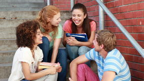 Happy students sitting on steps chatting Royalty Free Stock Photos