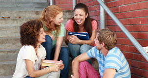 Happy students sitting on steps chatting Stock Images