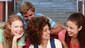 Happy students sitting on steps smiling at camera Stock Photography