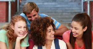Happy students sitting on steps smiling at camera Royalty Free Stock Images