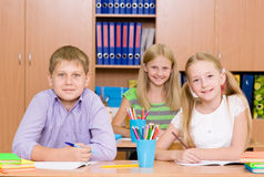 Happy students sitting at their desks in the classroom Stock Photo