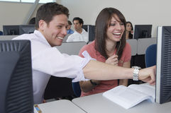 Happy Students Sitting Together At Computer Desk. Female student laughing while men showing something on computer screen with classmates in the background Stock Images