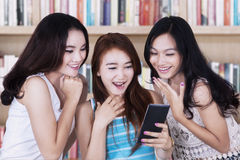 Happy students with smartphone in library Stock Photo