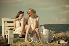 Happy students smiling with book and typewriter on blue sky. Summer holidays and vacation. Education and knowledge concept. Two girls sitting on bench on hay Stock Images