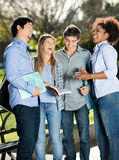 Happy Students Standing In Campus. Happy university students with books and mobilephone standing in campus Royalty Free Stock Photos