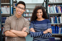 Happy students standing in library Royalty Free Stock Image