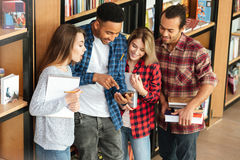 Happy students standing in library using mobile phone. Picture of young happy students standing in library using mobile phone. Looking aside Stock Images